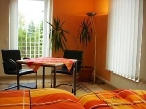 Schlafbereich I der Ferienwohnung mit Sitzgelegenheit und Tisch