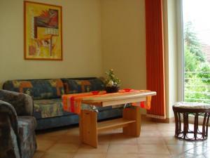 Wohnbereich der Ferienwohnung mit Sofa und Blick in den Garten